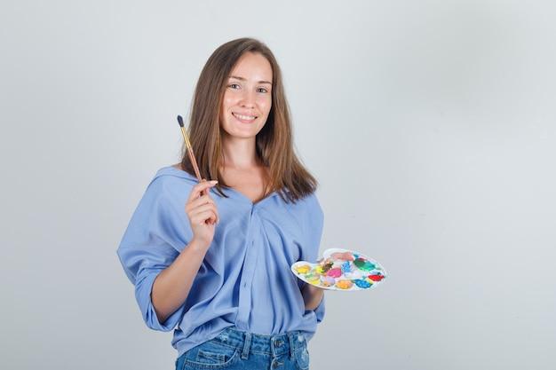 Młoda kobieta trzyma pędzel i paletę w niebieskiej koszuli, spodenkach i optymistycznie patrząc