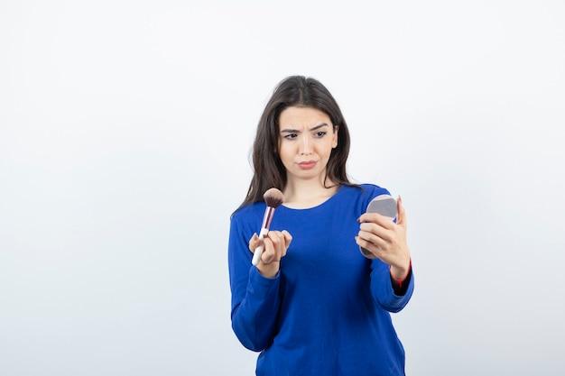 Młoda kobieta trzyma pędzel i patrząc w lustro.