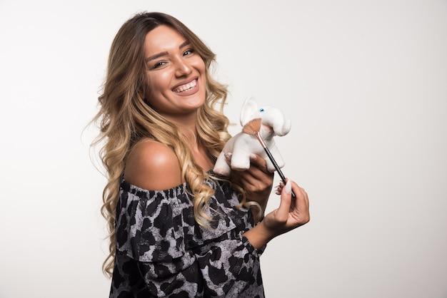Młoda kobieta trzyma pędzel i zabawkę słonia na białej ścianie.