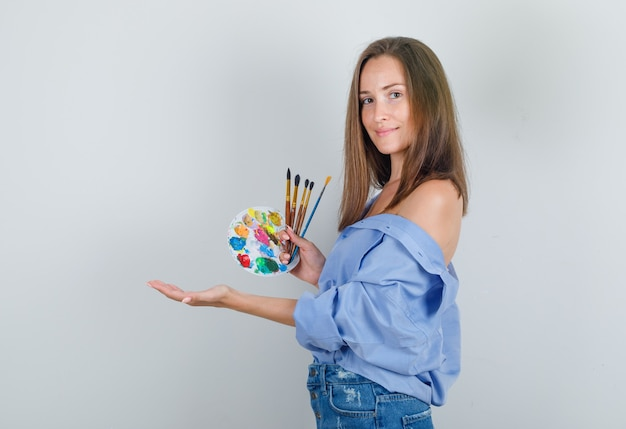 Młoda kobieta trzyma pędzle i paletę w koszuli, spodenkach i zadowolony patrząc