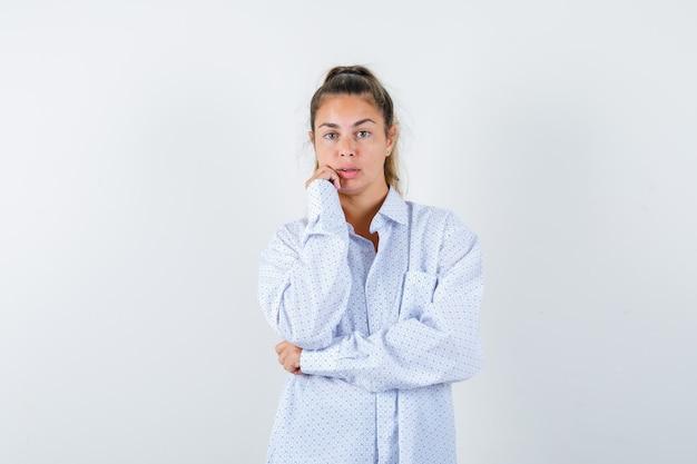 Młoda kobieta trzyma pięść w pobliżu ust w białej koszuli i wygląda pewnie