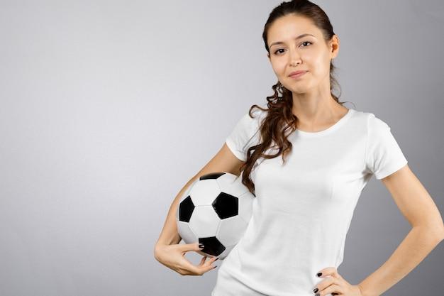 Młoda kobieta trzyma piłkę nożną na dłoni