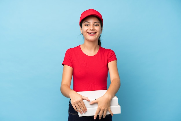 Młoda kobieta trzyma pizzę nad odosobnioną menchii ścianą z niespodzianka wyrazem twarzy