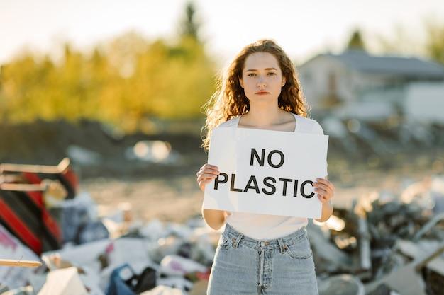 Młoda kobieta trzyma plakat. napis no plastic. pokazuje znak protestujący przeciwko zanieczyszczeniu plastikiem.