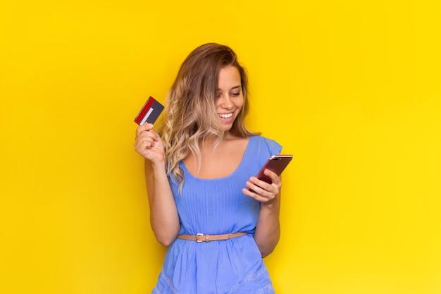 Młoda kobieta trzyma plastikowy kredyt, patrząc na ekran telefonu komórkowego podczas dokonywania zakupu online