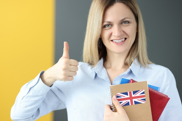 Młoda kobieta trzyma podręcznik do angielskiego i pokazuje kciuk do góry