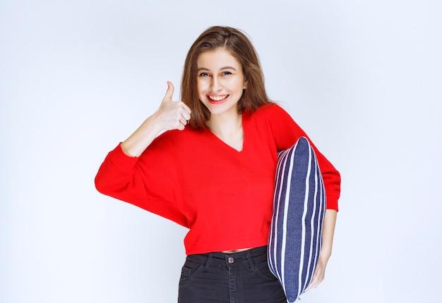 Młoda kobieta trzyma poduszkę w niebieskie paski i pozytywne samopoczucie.