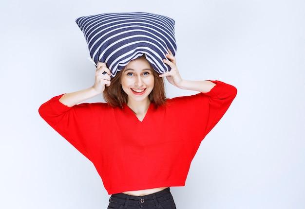 Młoda kobieta trzyma poduszkę w niebieskie paski nad głową.