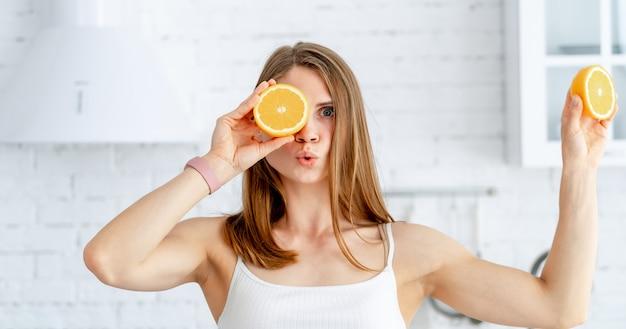 Młoda kobieta trzyma połówkę pomarańcze blisko jej pięknej twarzy w kuchni. koncepcja zdrowej żywności.