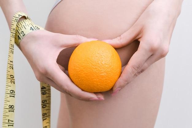 Młoda kobieta trzyma pomarańczę i miarkę na jasnym tle. koncepcja problemu cellulitu