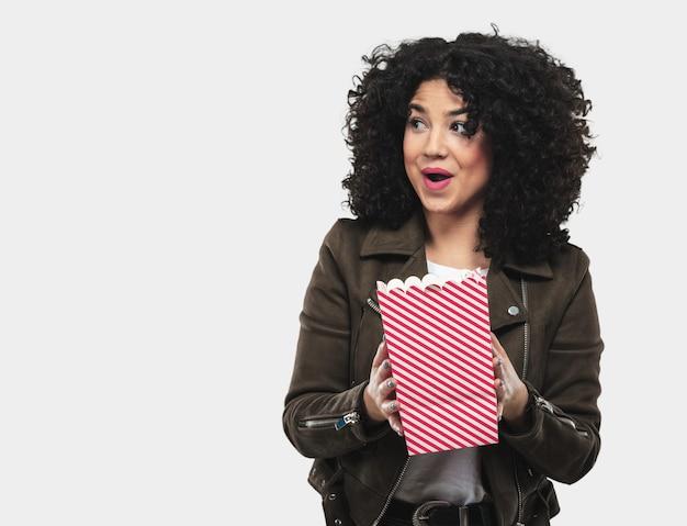 Młoda kobieta trzyma popcorn