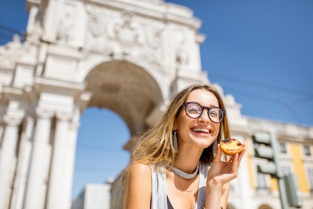 Młoda kobieta trzyma portugalskie ciasto tarta jajeczna o nazwie pastel de nata na zewnątrz na tle łuku triumfalnego w lizbonie