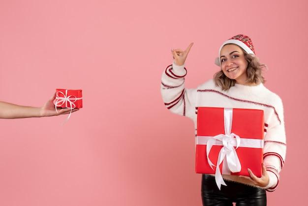 Młoda kobieta trzyma prezent i przyjmuje prezent od mężczyzny na różowo
