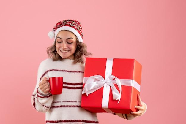 Młoda kobieta trzyma prezent świąteczny i filiżankę herbaty na różowo