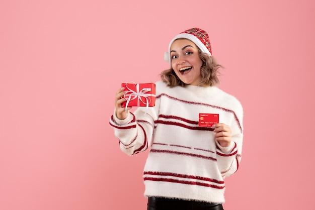 Młoda kobieta trzyma prezent świąteczny i kartę bankową na różowo