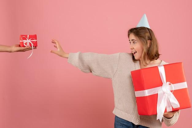 Młoda kobieta trzyma prezent świąteczny i przyjmuje prezent od mężczyzny na różowo