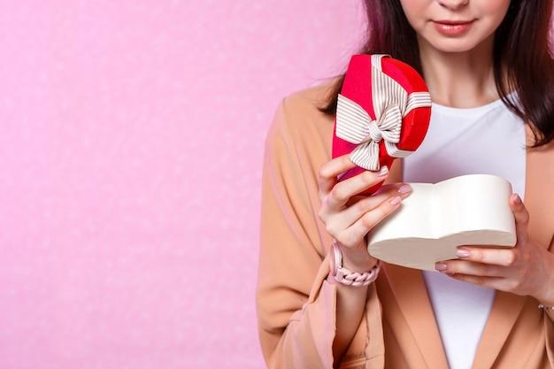 Młoda kobieta trzyma prezent w kształcie serca