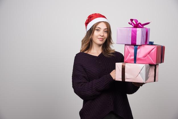Młoda kobieta trzyma prezentów pudełka z santa kapeluszowymi prezentami.