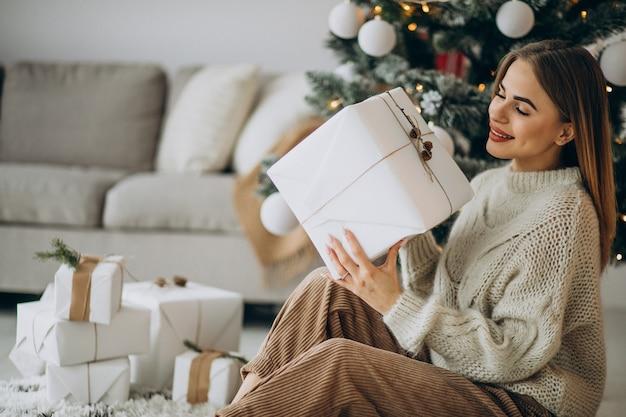 Młoda kobieta trzyma prezenty świąteczne i siedzi pod choinką