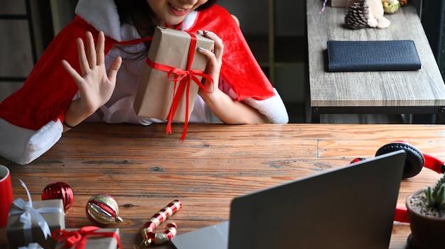 Młoda kobieta trzyma prezenty świąteczne i wideorozmowa z przyjaciółmi.