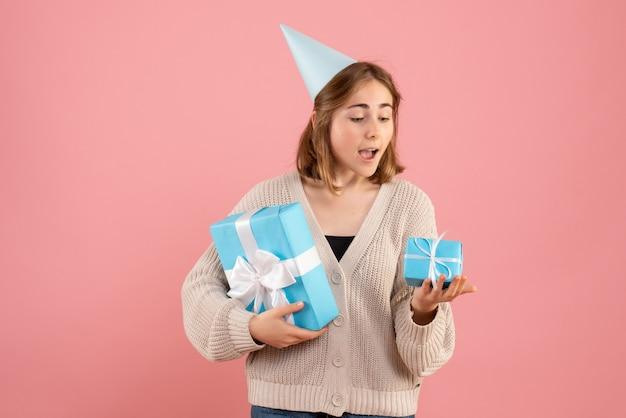 Młoda kobieta trzyma prezenty świąteczne na różowo