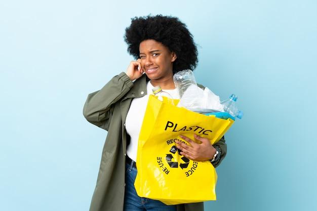 Młoda kobieta trzyma przetwarzającą torbę odizolowywająca na kolorowych udaremniających i zakrywających ucho
