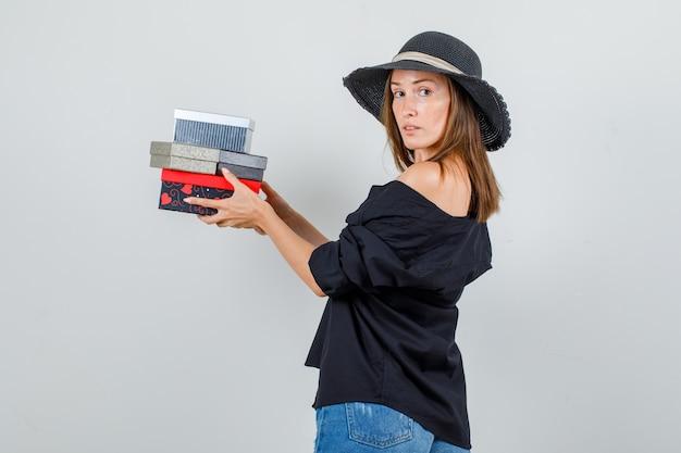 Młoda kobieta trzyma pudełka na prezenty, patrząc w koszulę, spodenki, kapelusz.