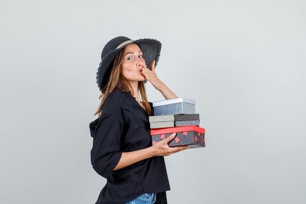 Młoda kobieta trzyma pudełka na prezenty podczas wysyłania buziaka w koszuli, spodenkach, kapeluszu.