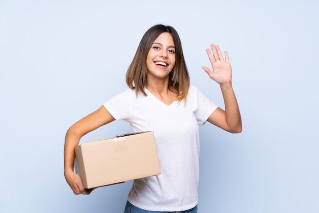 Młoda kobieta trzyma pudełko, aby przenieść go do innej witryny i pozdrawiając