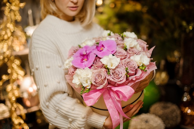 Młoda kobieta trzyma pudełko różowych róż i orchidei ozdobionych białym jaśminem