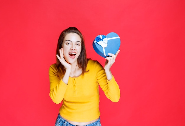 Młoda kobieta trzyma pudełko upominkowe w kształcie niebieskiego serca i czuje się zaskoczona
