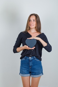 Młoda kobieta trzyma pudełko w czarnej koszuli, dżinsy szorty