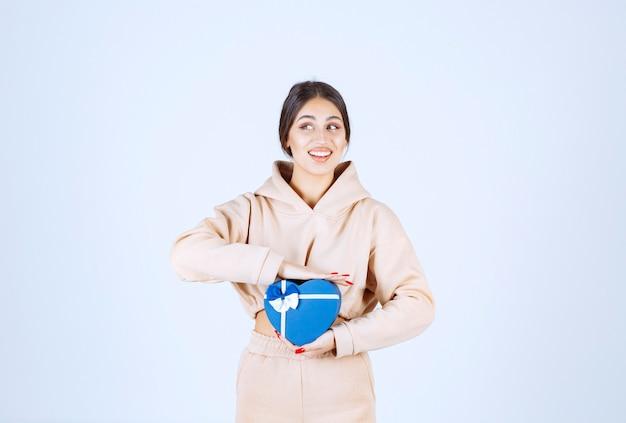 Młoda kobieta trzyma pudełko w kształcie serca niebieskie i wygląda na szczęśliwego