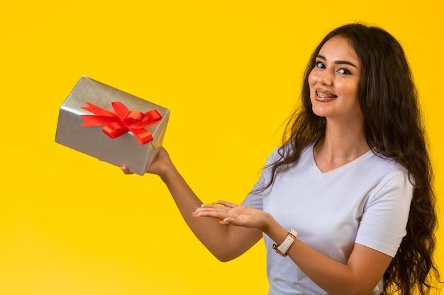 Młoda kobieta trzyma pudełko z czerwoną kokardą