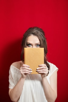 Młoda kobieta trzyma pustą książkę w skórzanej okładce na tle czerwonych zasłon