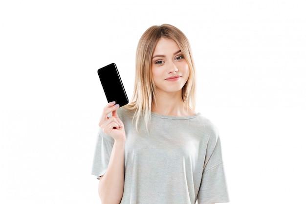 Młoda kobieta trzyma pustego scren telefon komórkowego i patrzeje kamerę