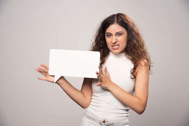 Młoda kobieta trzyma pusty pusty biały plakat mowy. wysokiej jakości zdjęcie