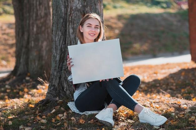 Młoda kobieta trzyma ramę z copyspace