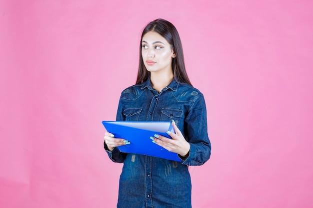 Młoda kobieta trzyma raport biznesowy i myślenia