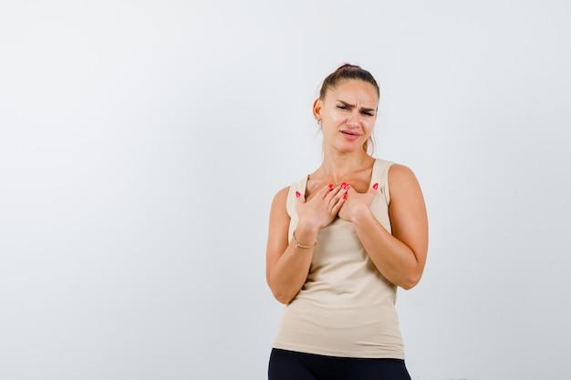 Młoda kobieta trzyma ręce na klatce piersiowej w beżowym podkoszulku i wygląda z nadzieją. przedni widok.