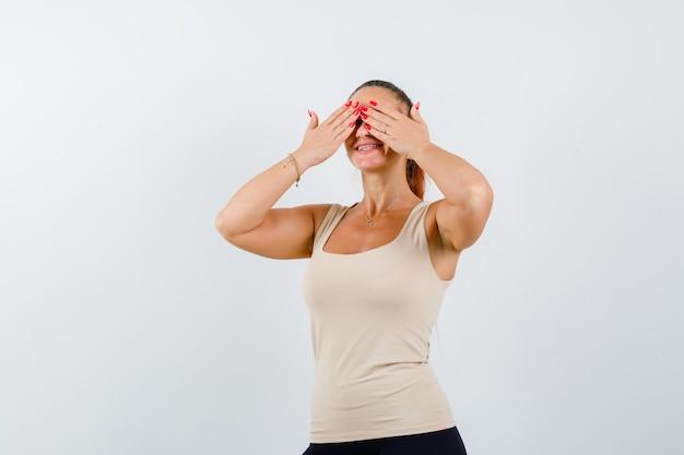 Młoda kobieta trzyma ręce na oczach w beżowym bezrękawniku i wygląda uroczo. przedni widok.