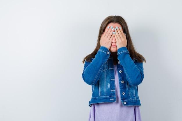 Młoda kobieta trzyma ręce na oczach w koszulce, kurtce i wygląda na przestraszoną. przedni widok.