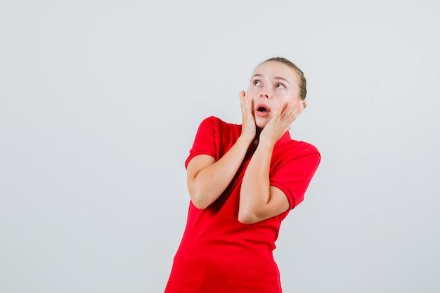 Młoda kobieta trzyma ręce na policzkach w czerwonej koszulce i wygląda przestraszony