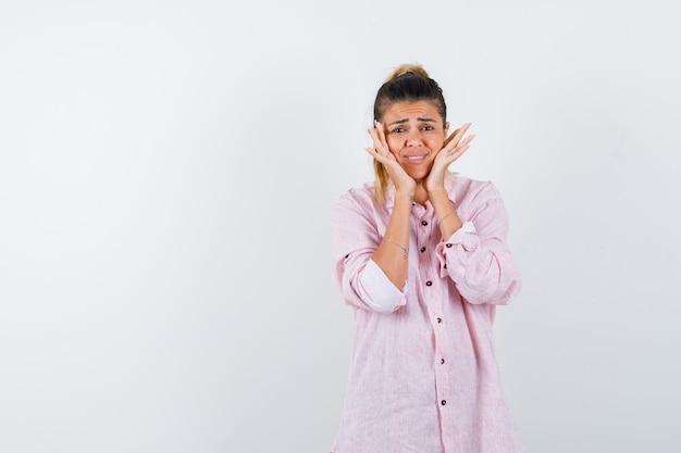 Młoda kobieta trzyma ręce na policzkach w różowej koszuli i wygląda zmartwiony