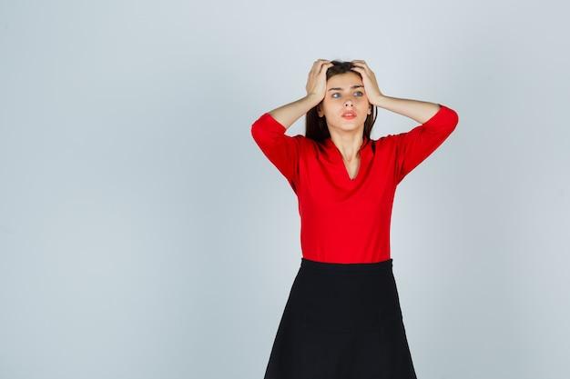 Młoda kobieta trzyma ręce na skroniach w czerwonej bluzce, czarnej spódnicy i wygląda zmartwiony