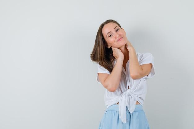 Młoda kobieta trzyma ręce na szyi w białej bluzce i jasnoniebieskiej spódnicy i wygląda uroczo