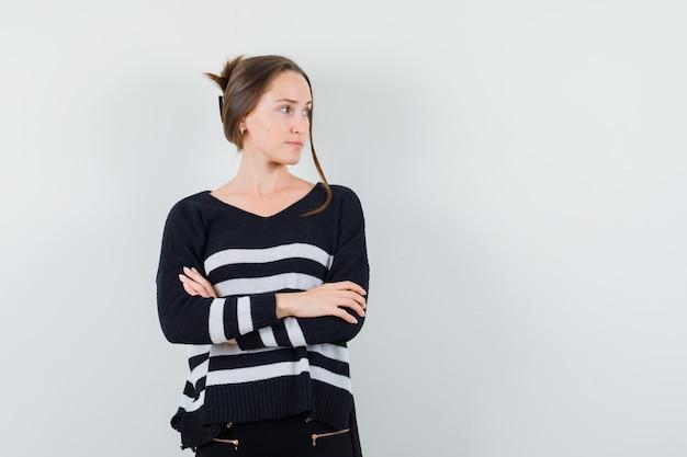 Młoda kobieta trzyma ręce skrzyżowane w dzianinie w paski i czarne spodnie i wygląda pewnie