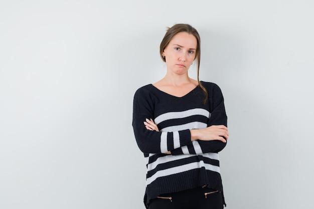Młoda kobieta trzyma ręce skrzyżowane w dzianinie w paski i czarne spodnie i wygląda poważnie