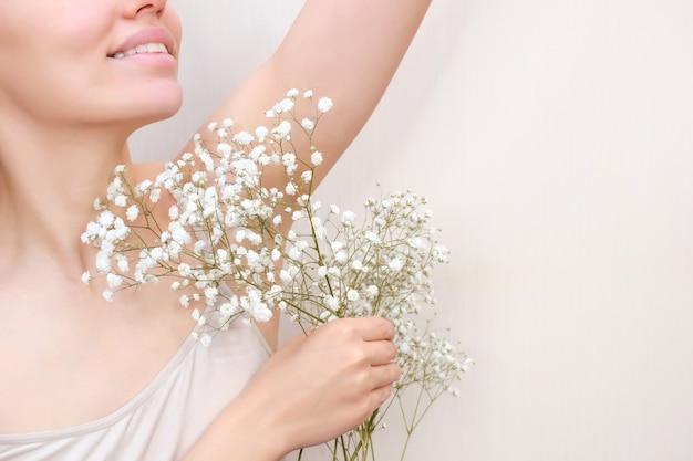 Młoda kobieta trzyma ręce w górze i pokazuje pachy z gipsówką w dłoni, pachy gładką przezroczystą skórą. dziewczyna pokazuje czystą pachę. piękno portret. depilacja i depilacja.