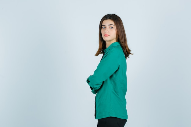 Młoda kobieta trzyma ręce złożone w zielonej koszuli i wygląda rozsądnie.